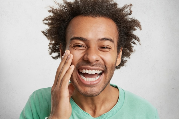 Positiviteit en prettige emoties concept. blij man met een donkere, gezonde huid grijnst