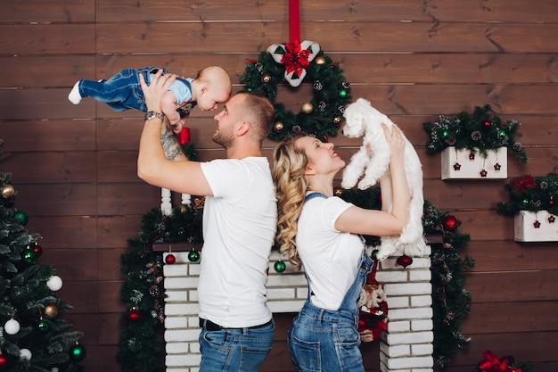 Positiviteit familie poseren samen in de buurt van open haard en presenteert voor kerstmis