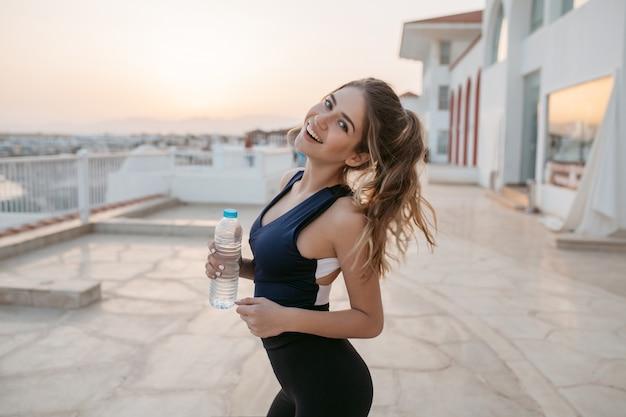 Positiviteit, geluk uitdrukken van vrolijke jonge vrouw op training aan de kust in de vroege zonnige ochtend. aantrekkelijk figuur, modieuze sportieve vrouw, zomertijd in tropisch land