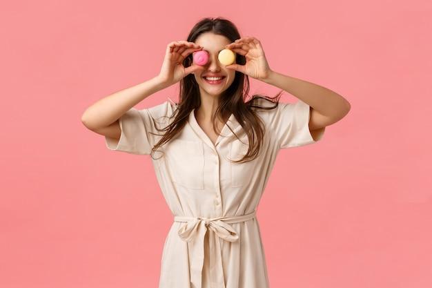 Positiviteit, heerlijk eten en emoties concept. gelukkig en zorgeloos europees meisje houdt van snoep eten, ogen van macarons maken en vrolijk glimlachen, roze muur blij maken