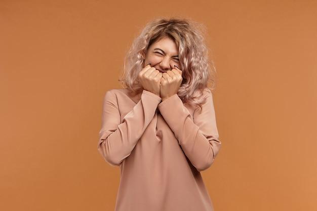 Positiviteit, vreugde en geluk concept. shot van vrolijke dolblij hipster meisje in stijlvolle kleding gelukkig lachend, hand in hand op haar mond