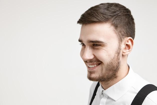 Positiviteit, vreugde, geluk en echte menselijke emoties. portret van knappe jonge bebaarde zakenman in wit overhemd met bretels, verheugend op de resultaten en voordelen van zijn zakelijk project