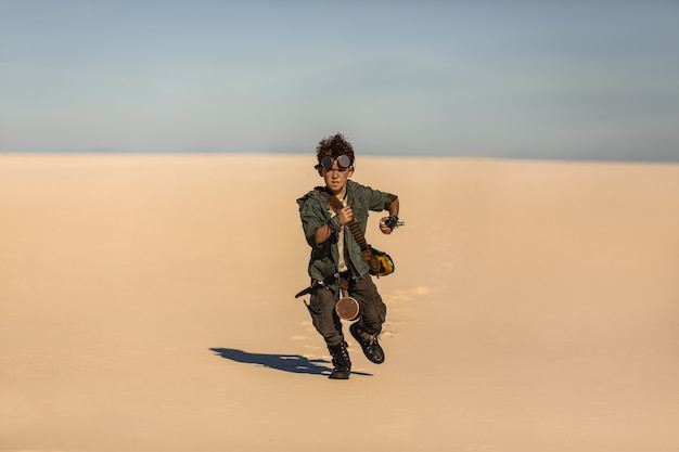 Post-apocalyptische warrior boy outdoors in desert wasteland