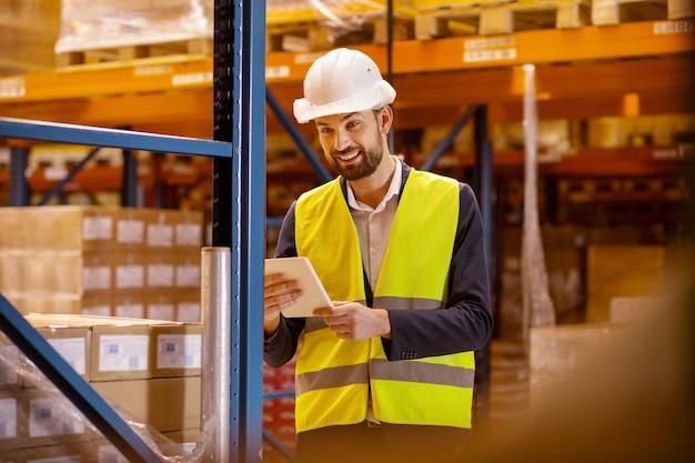 Postbode. blij gelukkig man met behulp van een tablet tijdens het kiezen van een doos voor bezorging