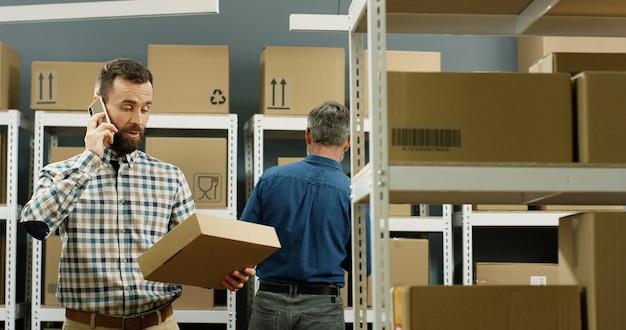 Postbode die zich in postopslag met pakketten bevindt en op mobiele telefoon spreekt. mannelijke arbeider die op cellphone spreekt en pakket in leveringsruimtehoogtepunt houdt van dozen.
