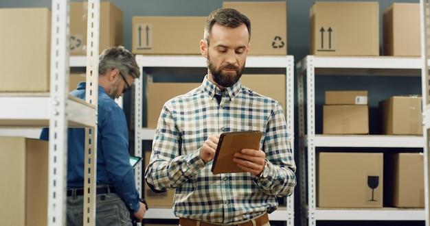 Postbode die zich in postopslag met pakketten bevindt en op tabletcomputer tikt.