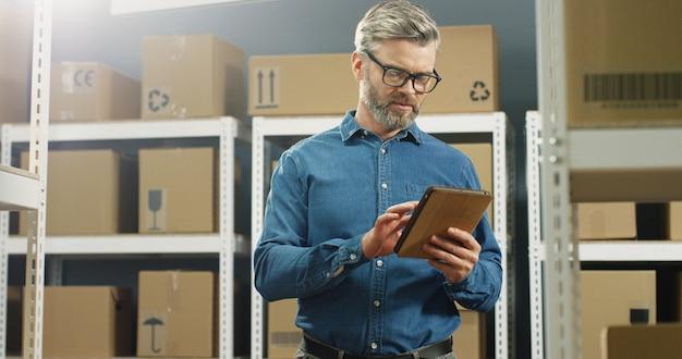Postbode in glazen die zich in postopslag met pakketten bevinden en op tabletcomputer onttrekken. mannelijke arbeider met computer die registratie in leveringshoogtepunt van dozen doen.