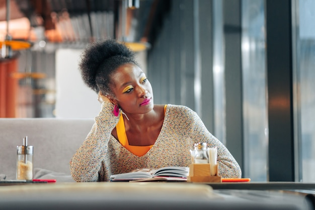 Postdoctorale student. krullende donkerharige slimme postdoctorale student die hard studeert in de cafetaria