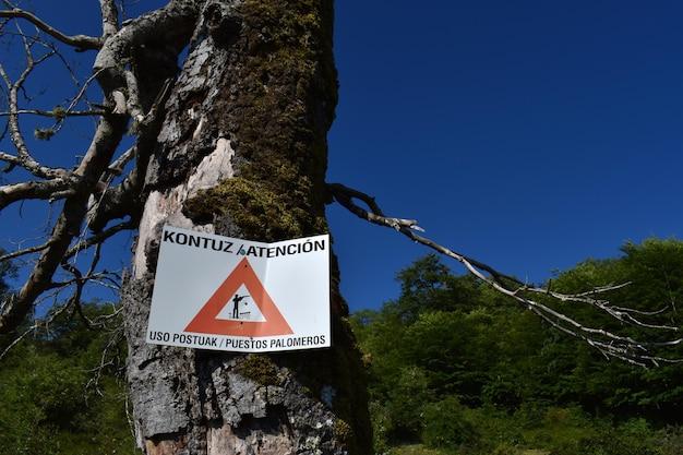 Poster die waarschuwt voor het gevaar aangezien het een duivenjachtgebied is, geschreven in het spaans en baskisch.