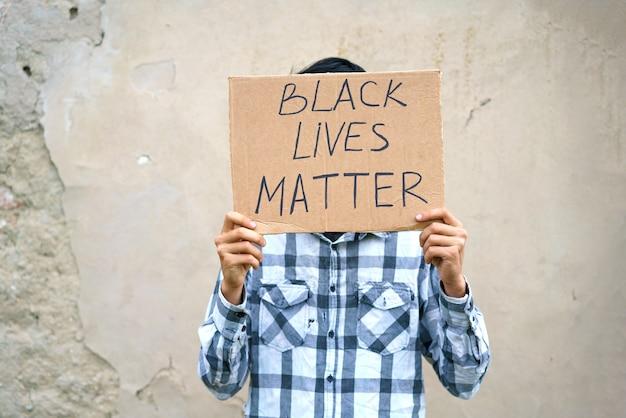 Poster waarop staat dat het zwarte leven ertoe doet in de handen van een jonge man, een blanke man voerde een protestdemon op...