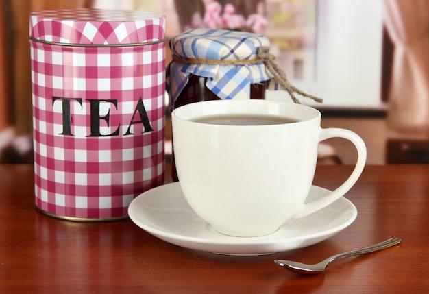 Pot en kopje thee op tafel in de kamer