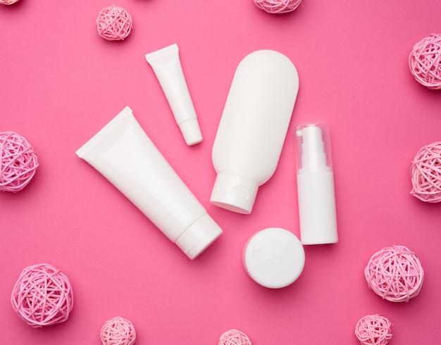 Pot, fles en lege witte plastic buizen voor cosmetica op een roze achtergrond. verpakking voor crème, gel, serum, reclame en productpromotie, mock-up