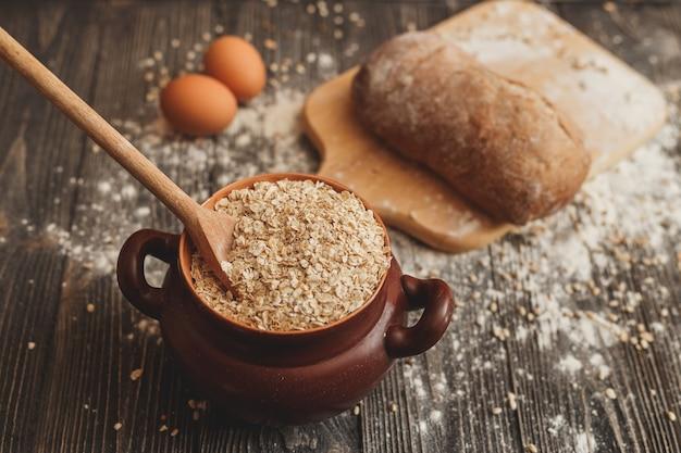 Pot gevuld met havermout op tafel met een lepel, eieren en brood