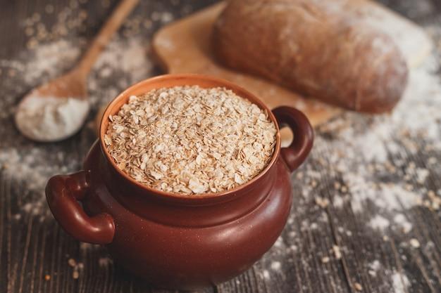 Pot gevuld met havermout op tafel met een lepel en zelfgebakken brood