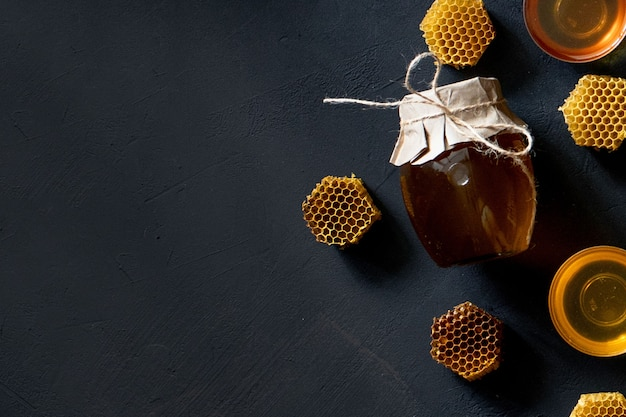 Pot honing met honingraat op zwarte tafel, bovenaanzicht. ruimte voor tekst.