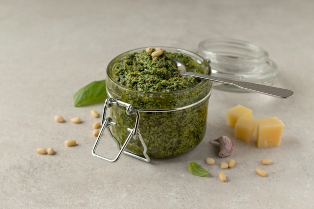Pot klassieke italiaanse pestosaus met lepel en ingrediënten op grijze tafel