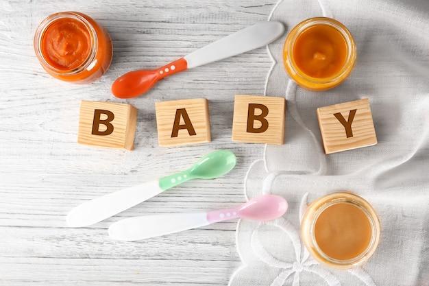 Pot met babyvoeding op houten tafel
