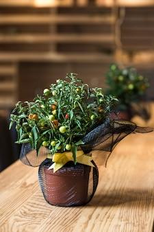 Pot met bloemen op een houten tafel met een groene plant in het interieur