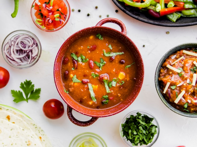 Pot met chili naast mexicaanse snacks