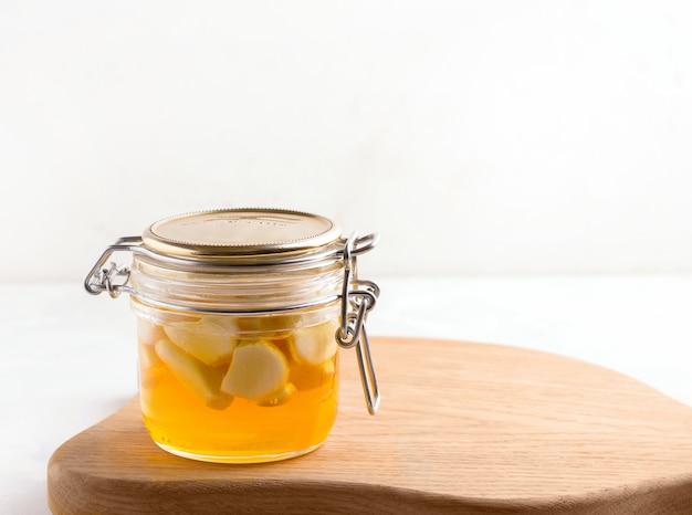 Pot met gefermenteerde honing op een houten bord. ruimte kopiëren. witte achtergrond