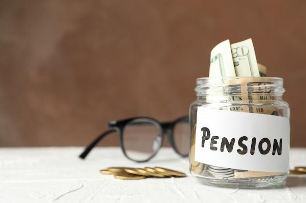 Pot met geld en inscriptie pensioen tegen bruin oppervlak