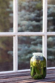 Pot met gezouten komkommers staande op oude houten tafel tegen terrasraam. oogstseizoen en zelfgemaakte jam. verticaal formaat, kopieer ruimte. ingemaakte groenten