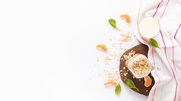 Pot met haver; basilicum blaadjes; stukjes sinaasappel; melk en servet op witte achtergrond