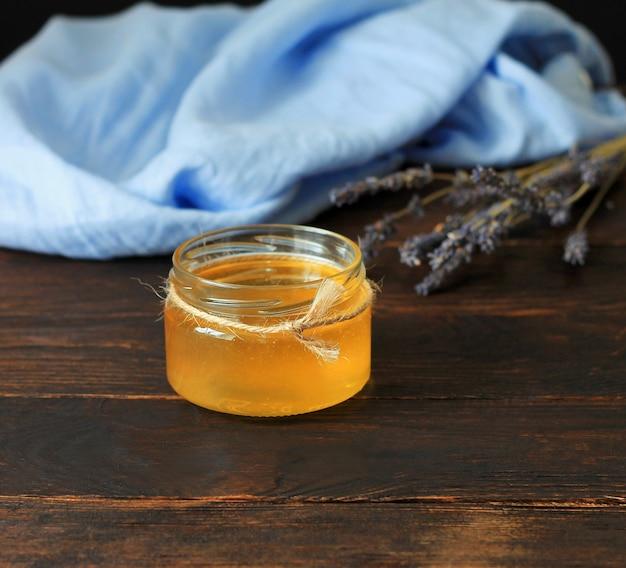 Pot met honing en bosje droge lavendel over oude houten tafel