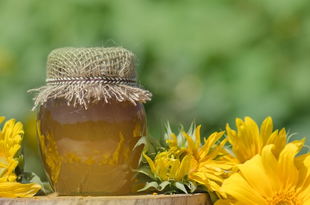 Pot met honing en zonnebloemen op houten tafel over bokeh tuin achtergrond