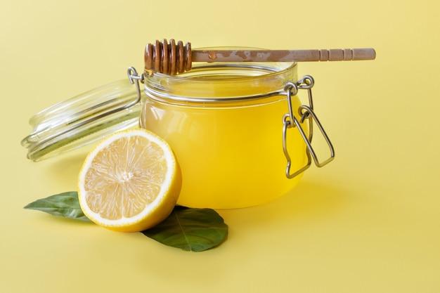 Pot met honing met citroen op gele achtergrond
