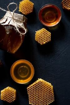 Pot met honing met honingraat op zwarte lijst