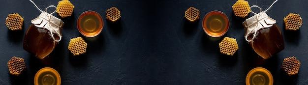 Pot met honing met honingraat op zwarte tafel, bovenaanzicht. ruimte voor tekst.