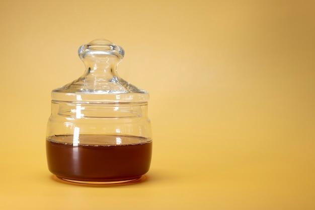 Pot met honing op een felgele achtergrond in de stijl van een reclamevoedselfoto. horizontaal