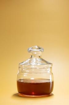 Pot met honing op een felgele achtergrond in de stijl van een reclamevoedselfoto. verticaal
