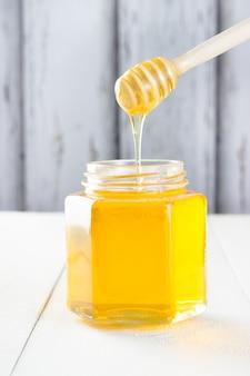 Pot met honing op houten tafel.