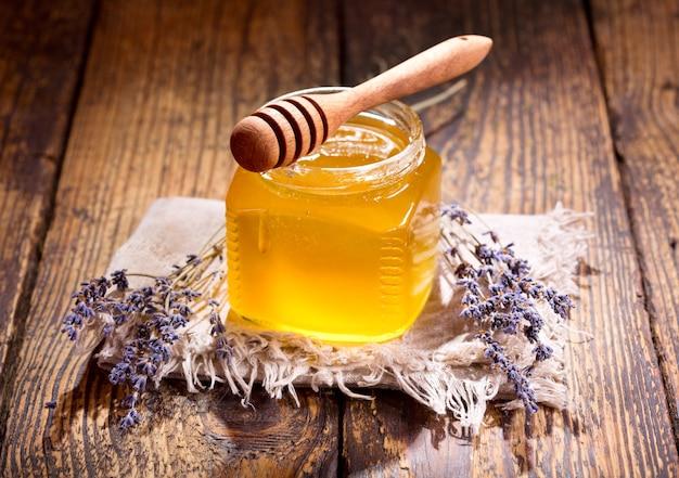 Pot met honing van lavendel op houten tafel