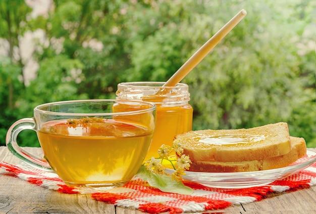 Pot met lindehoning, kopje linde-thee en lindebloemen op houten tafel op een zonnige dag