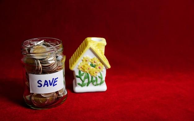 Pot met munten en bewaar label met investeringen in huisbezit om geld te besparen voor de toekomst