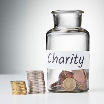 Pot met munten en stapels besparingen op bureau