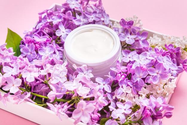 Pot met natuurlijke gezichtscrème met lila bloemen op roze achtergrond