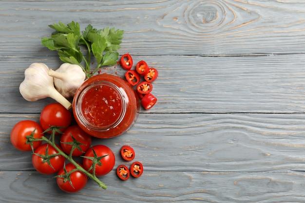 Pot met rode chili en tomatensaus en kruiden op houten tafel