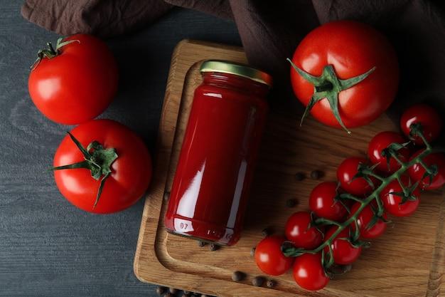 Pot met tomatenpuree en tomaten op houten tafel