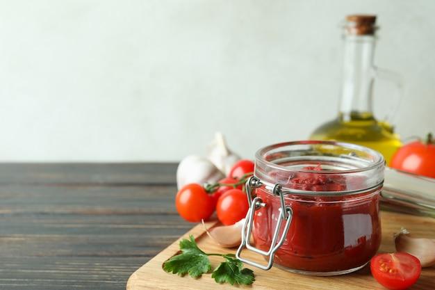 Pot met tomatenpuree op houten tafel met ingrediënten