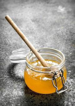 Pot met verse honing op rustieke tafel.