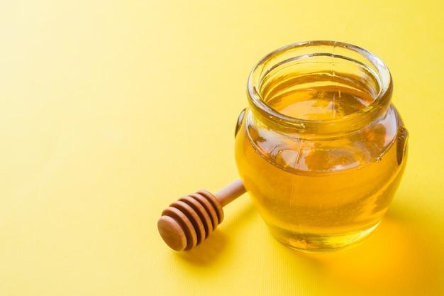 Pot met vloeibare honing en een stok op gele ondergrond. kopieer ruimte.