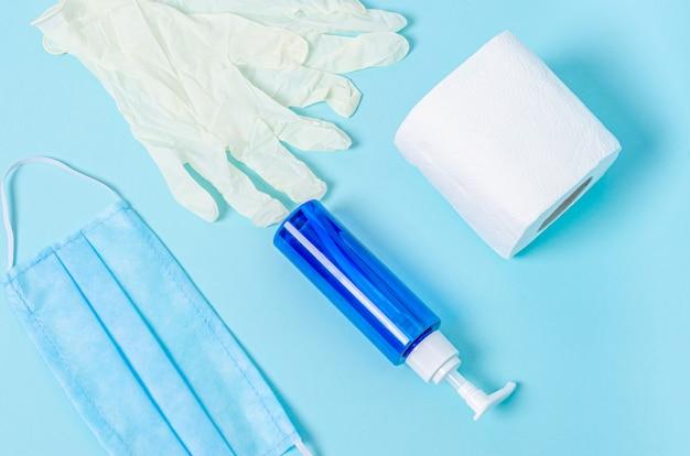 Pot met vloeibare zeep, toiletpapier, beschermend medisch masker, witte rubberen handschoenen op een blauwe ondergrond