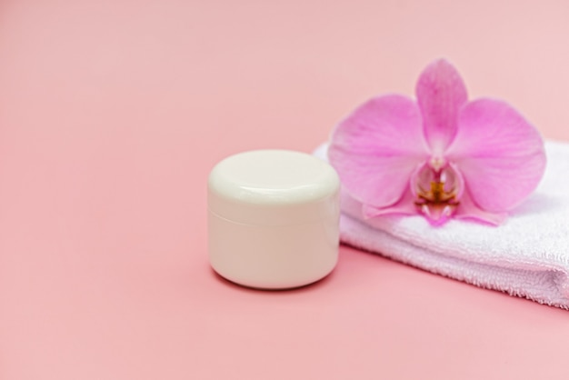 Pot met vochtinbrengende lichaamscrème, badhanddoek, orchideebloem op een pastelroze achtergrond. huidverzorging cosmetisch concept. zachte selectieve focus. ruimte kopiëren.