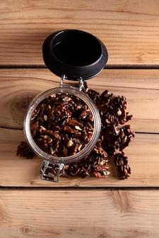 Pot met walnoten op een houten bord, bovenaanzicht