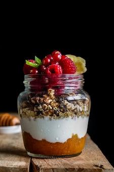 Pot met zelfgemaakte muesli met yoghurt, zelfgemaakte abrikozenjam en frambozen