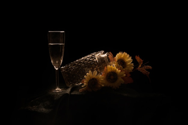 Pot met zonnebloemen en een glas champagne op tafel geïsoleerd op een zwarte achtergrond